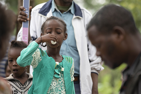 A young girl takes her antibiotics