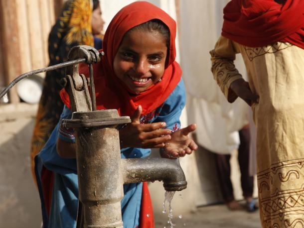 Children in Sindh, Pakistan, play at a water pump in a village.