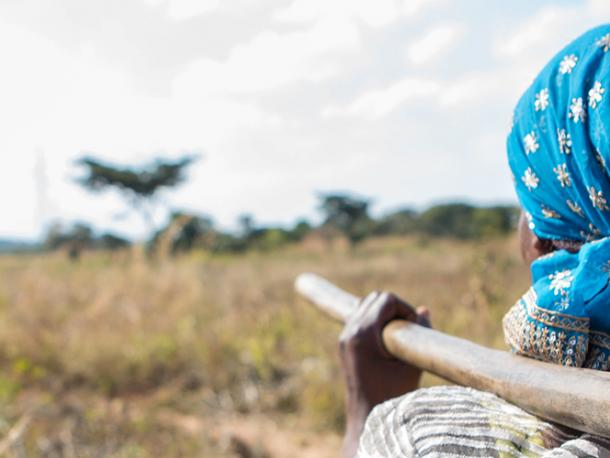 Florence, who with CAFOD's helplearned how to grow different crops to support herself on her own bit of land,going out into her farmland carrying a hoe.
