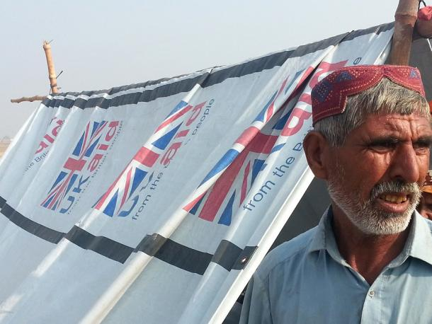 A Pakistani man stands outside a UK-funded temporary shelter after flooding in Sindh