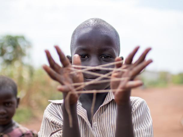 Boy in Uganda playing with string