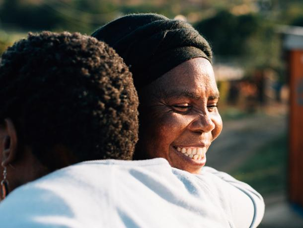 Two activists embrace in KwaMashu, an informal settlement north of Durban, South Africa. Christian Aid's partner, Church Land Programme, works closely with the shackdweller movement (Abahlali baseMjondolo) so that people in KwaMashu can live without fear