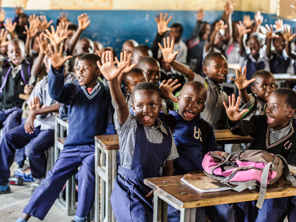 Children in school in Zambia raising their hands
