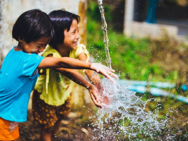 Two children playing with water in Chiang Mai, Thailand