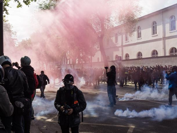 A protest with teargas and someone filming