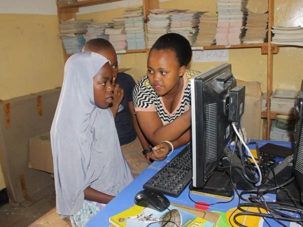 Tanzanian woman and child with computer learning about digital