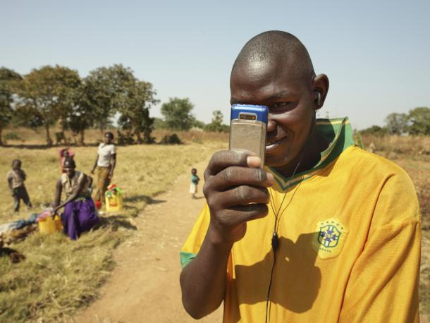 A young man holds a cell phone and takes a picture pointing it towards the camera, Mazabuka, Zambia
