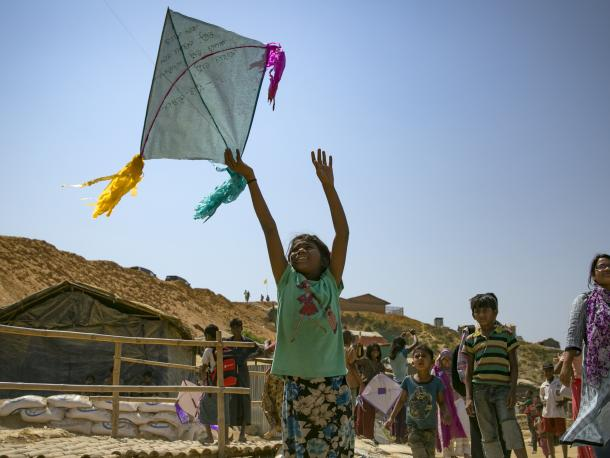 Girl playing with kite in refugee camp, Bangladesh