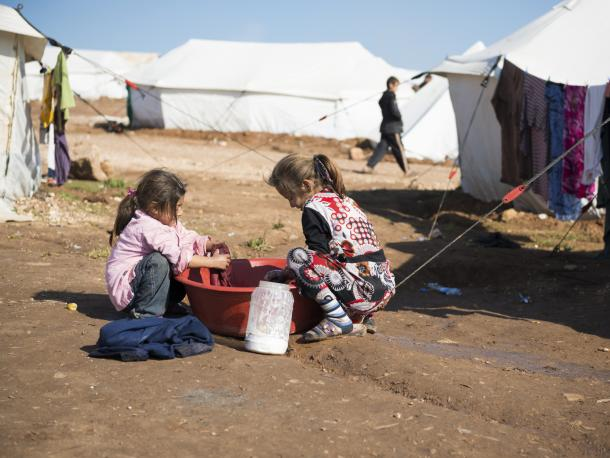 Atmeh, Syria - January 14, 2013: Two Syrian girls wash clothes outside their tent in the displaced persons camp in Atmeh, Syria. A boy walks by in the background.