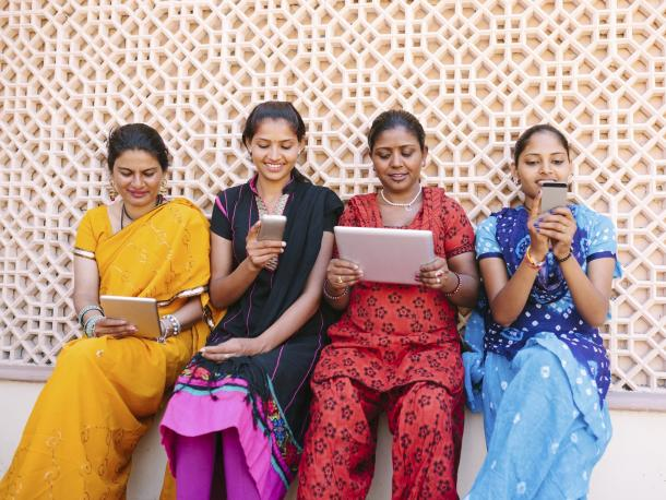 Four women using mobile devices