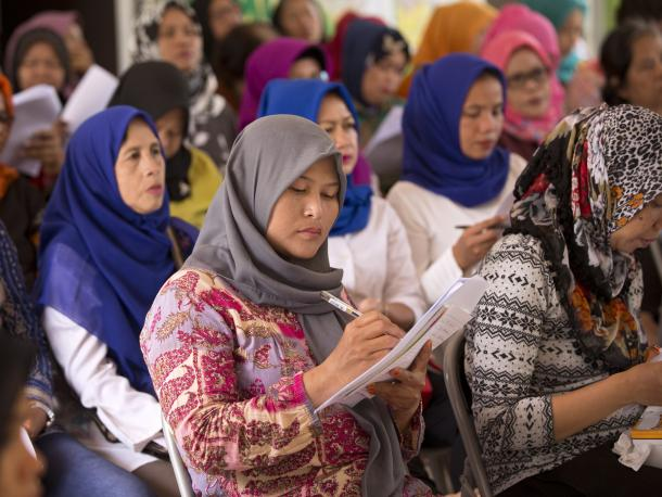 Women at community meeting holding paper