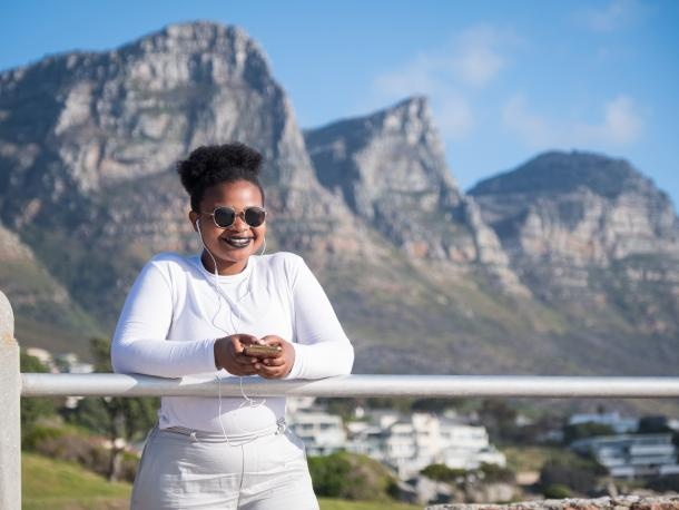 Woman standing in front of a mountain with headphones in