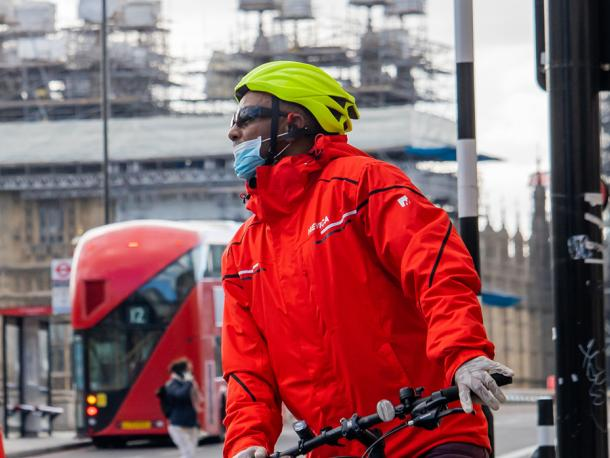 A man with his face covered cycles through London near parliament