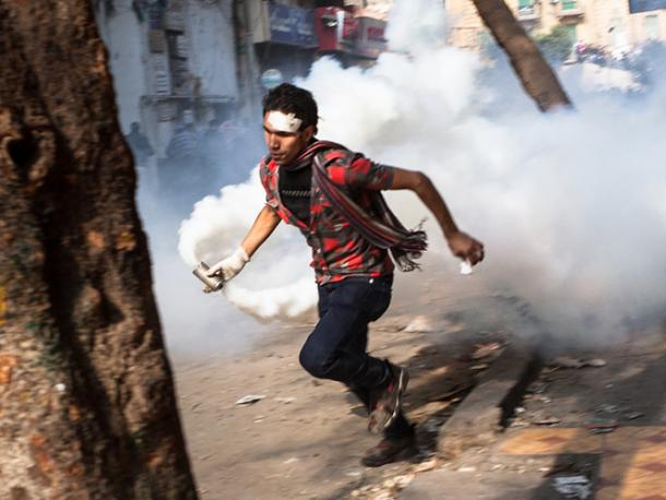 """Cairo, Egypt - November 23, 2011: A young man near Tahrir Square is running with a container of riot gas that the police just fired at the protestors."
