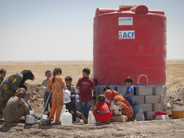 Kurdistan, Iraq - June 22, 2014: Women washing children and cloth at water tank. This camp is 15 km from Mosul away and it is set up on an empty field. This camp collects people from the region of Mosul after the ISIS invated the city.