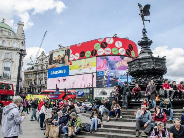 People in front of brand advertising screens at Piccadilly Circus