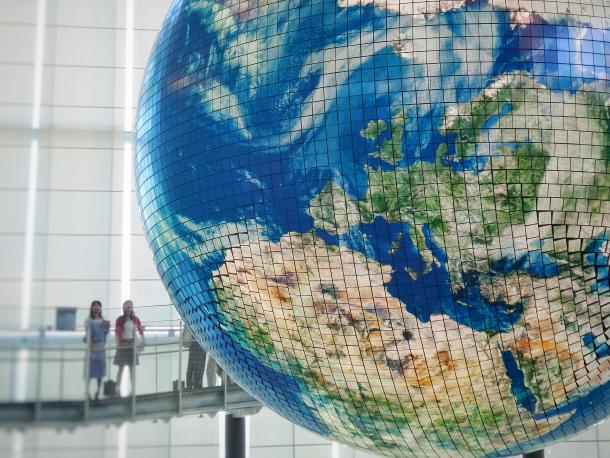 Two people standing next to large world map globe