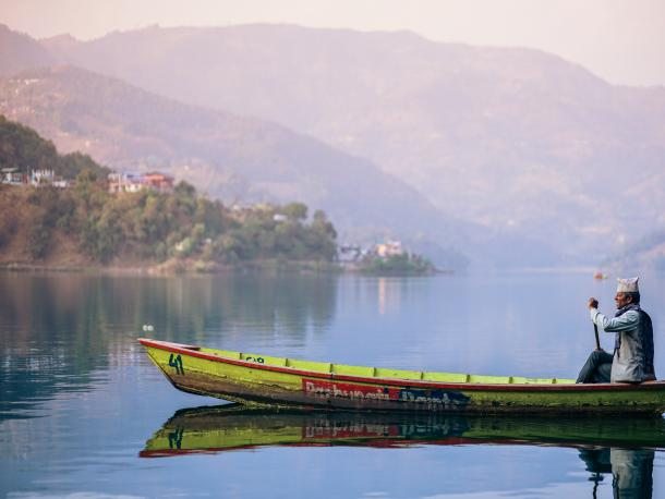 Man in canoe on lake in Nepal