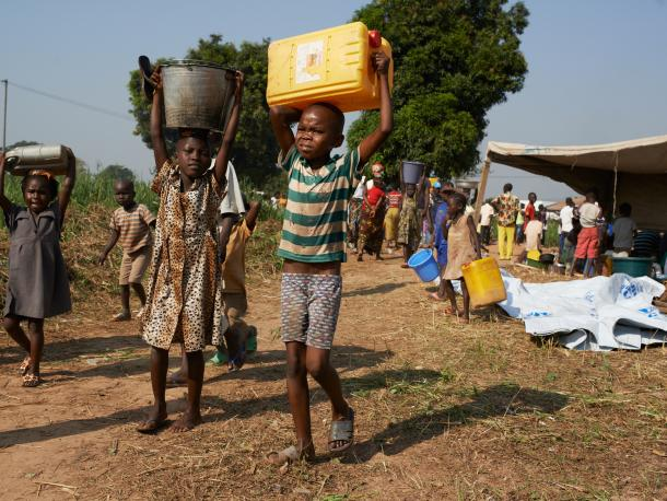 Akadus Zangoa carries a container of water to his mother in a camp in Central African Republic
