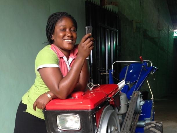 A woman in Nigeria with a Hello Tractor smart tractor