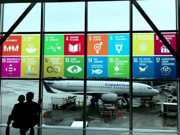 SDGS banner through an airport window with a plane
