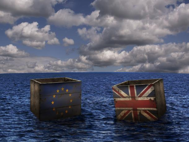 Two crates floating on the sea with the EU and UK flags