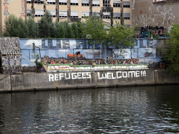Riverside designed as a boat and Refugees Welcome written on wall