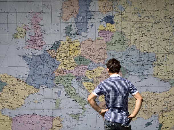 Man looking at Europe on a world map