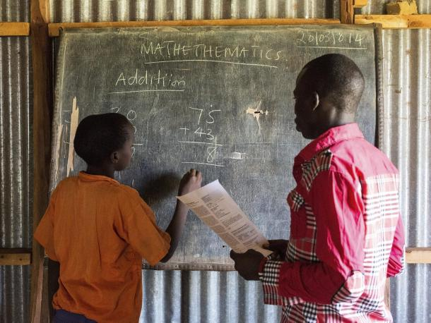 Student doing maths on the blackboard with teacher overseeing
