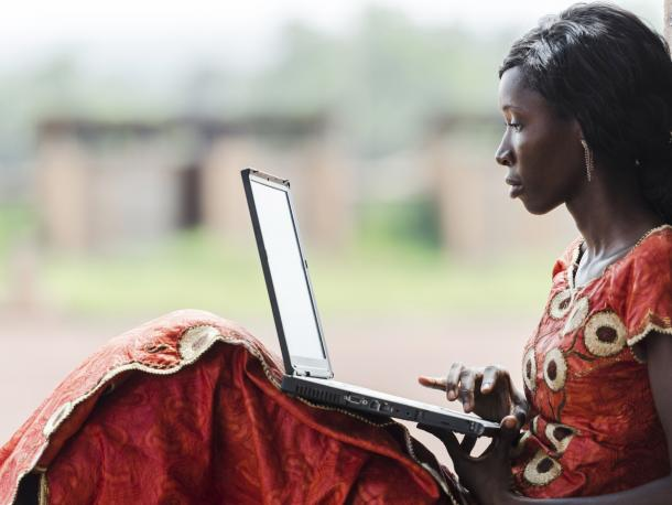 Woman in red print dress sitting on the ground with a laptop
