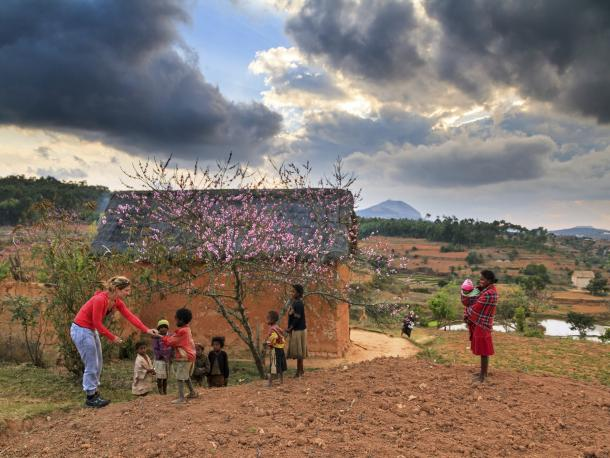 Rural village in Madagascar with clouds overhead and children with two adults