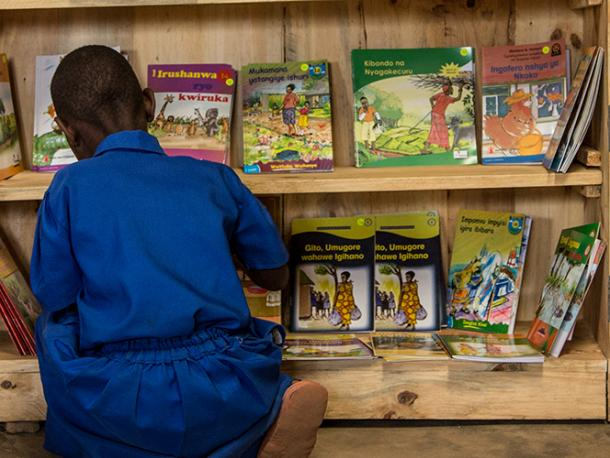 A student chooses a book from a cabinet at the Groupe Scolair Ruhanga school in Burera District of Rwanda.