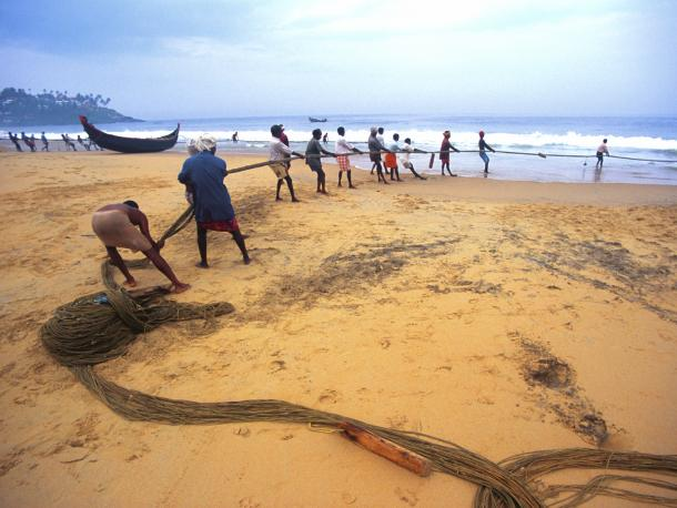 Team working together on the beach to pull in ropes from the sea