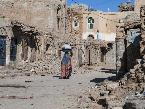 Woman walking through ruined area of Sana'a, Yemen