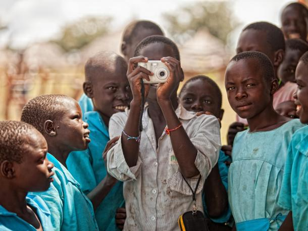 A young African boy taking a photo with a digital camera