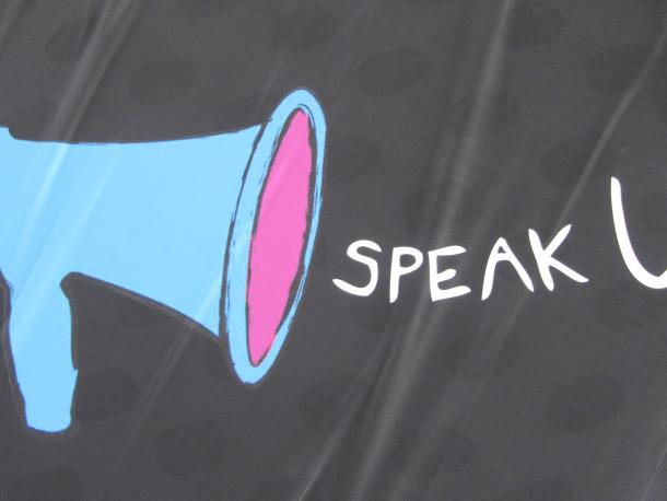 Megaphone and the words speak up on a banner