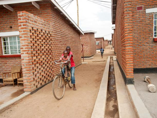 Two boys on a bike in new housing development in Malawi