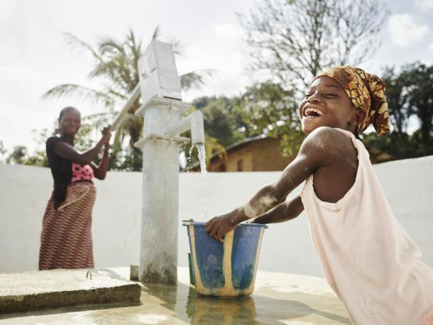Child collects water from pump in Sierra Leone