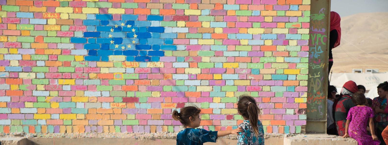 Children painting a wall mural with EU flag in Arbat camp, Iraq