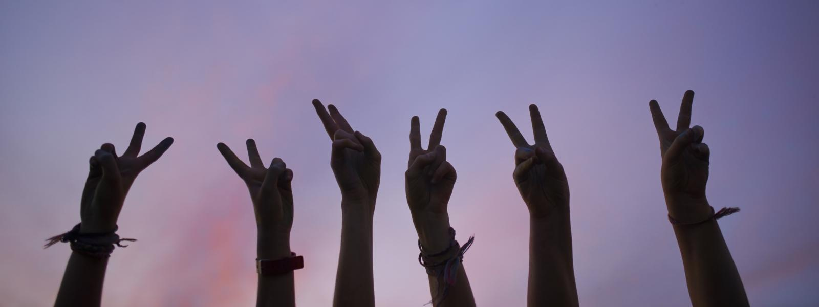 Six hands making the peace sign