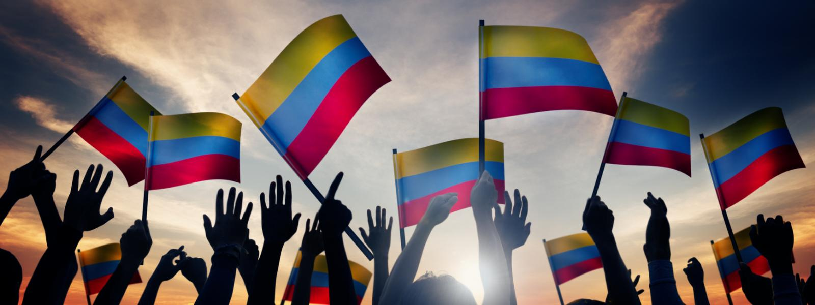 crowd holding Colombian flags