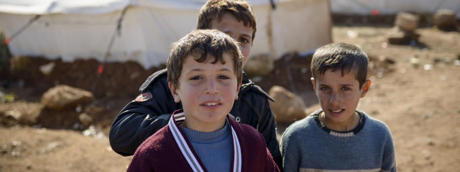 Qatma, Syria: Three boys stand in front of tents at a camp for displaced persons in northern Syria