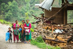 family beside a damaged house near Naglebhare, Nepal