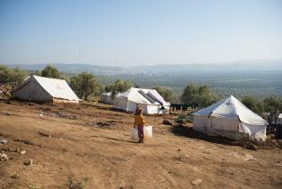 Two young girls stand outside some of the many tents housing internally displaced Syrians in an olive grove in Atmeh, Syria