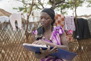 Hawa, refugee in a camp in Cameroon, with a clipboard