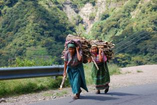 Two Guatemalan women walking back to the village to bring the wood collected to cook dinner for the family.