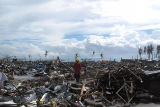 Man stands in destroyed Tacloban after Typhoon Haiyan