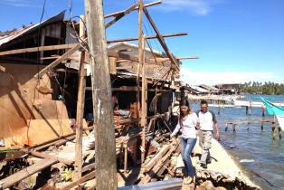 People through destroyed building after typhoon in Philippines